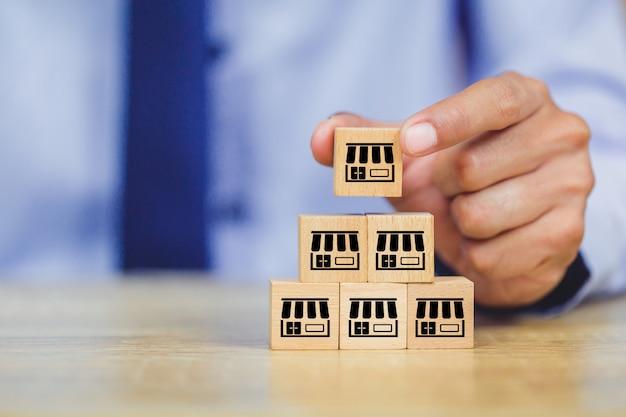 Рука бизнесмена выбирает деревянный блог с маркетингом франшизы. Premium Фотографии