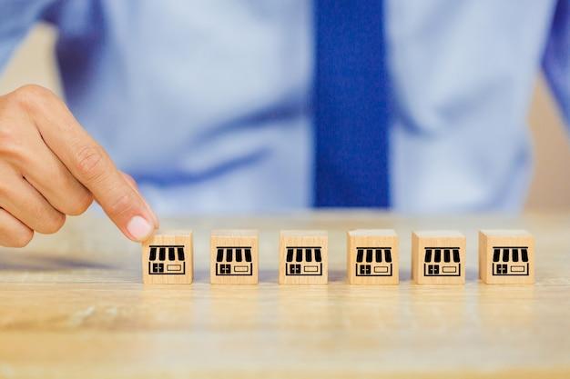 実業家の手は、フランチャイズマーケティングと木製のブログを選択します。 Premium写真