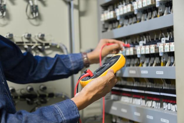 電気技師は、電気キャビネット制御の電力電線の電圧と電流を測定する作業テスターです。 Premium写真