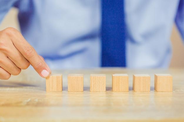木製のブロックを積み重ねるビジネスマンの手。 Premium写真