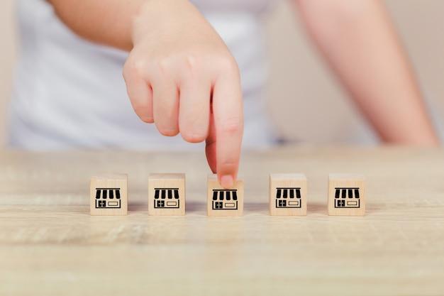 Концепция бизнеса франшизы, рука женщины выбирает деревянный блог с маркетингом франшизы. Premium Фотографии