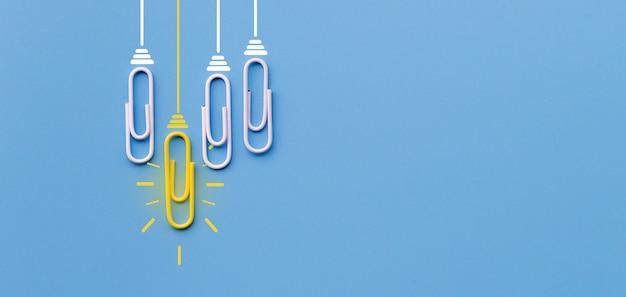 青色の背景にペーパークリップ思考創造性電球と素晴らしいアイデアコンセプト Premium写真