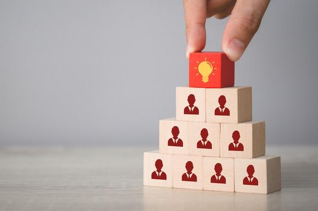 アイコン電球と人間のシンボル、創造的なアイデアと技術革新の概念と木製キューブを選択する手。 Premium写真