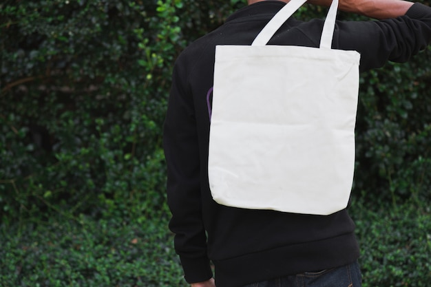 モックアップ、エコロジーコンセプトのバッグキャンバス生地を抱きかかえた。 Premium写真