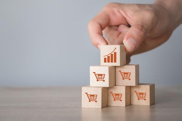Ручная сборка деревянных блоков со значком график и символом корзины покупок вверх, Premium Фотографии