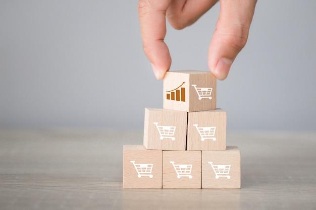 Ручная сборка складывает деревянный блок с иконкой график и символ корзины покупок вверх, Premium Фотографии