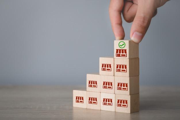 Бизнес-концепция франшизы, рука выбрать деревянный блог с маркетингом франшизы. Premium Фотографии