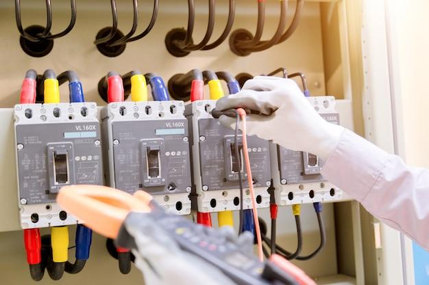 技術者は、コントロールパネルの電圧計で電圧または電流を測定しています Premium写真