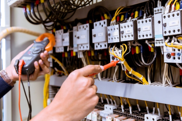 コントロールパネルの電流をマルチメータでテストする電気技師の測定。 Premium写真