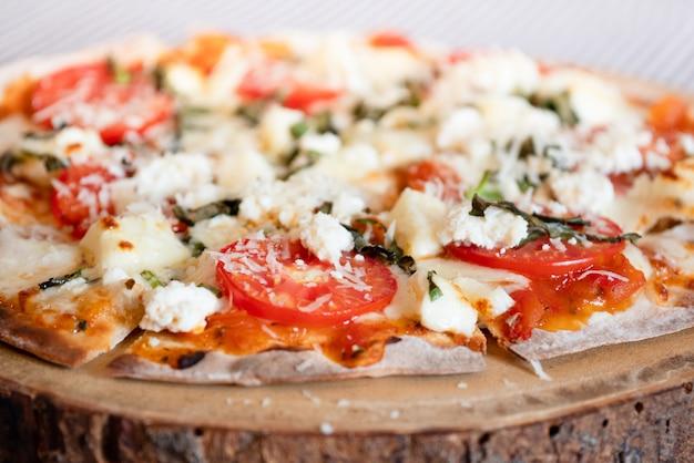 Домашняя хрустящая пицца на куске дерева, уютная кухня Premium Фотографии