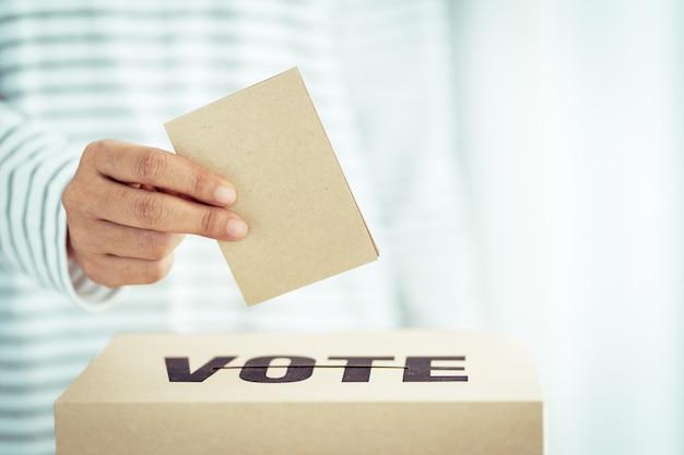 投票箱に茶色の紙を挿入 Premium写真