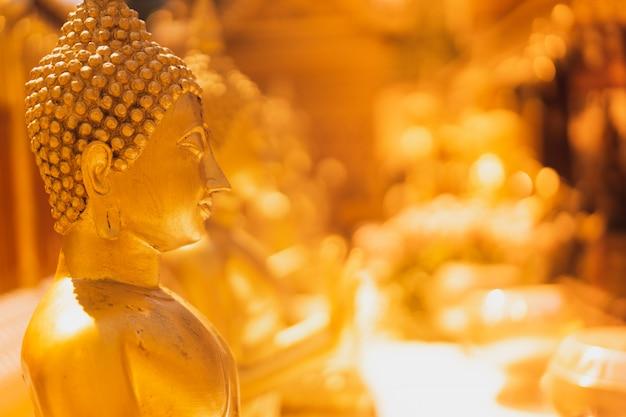 Золотая статуя будды с размытой золотой пагодой Premium Фотографии