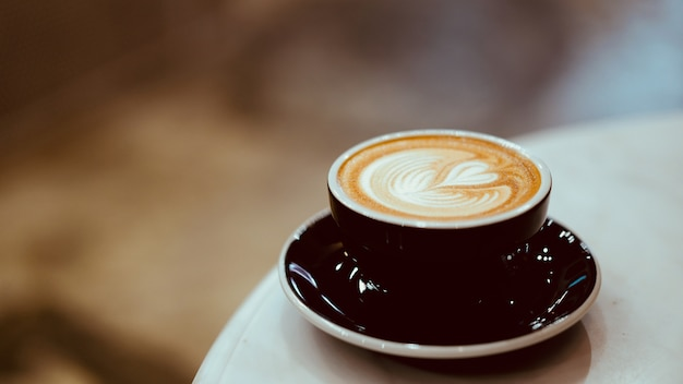 ハート形のラテアート、コーヒー愛好家の概念と熱いラテコーヒーのカップ Premium写真