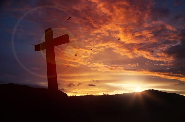 Крест на размытом фоне заката, Premium Фотографии