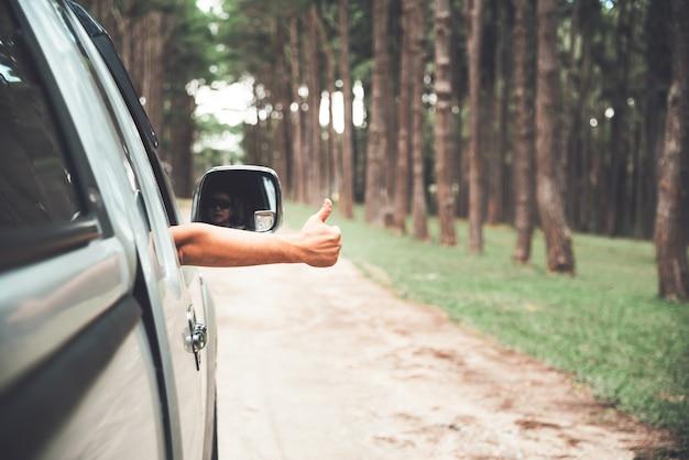 Мужчина за рулем пикапа, вытягивающий руку из машины отличный символ Premium Фотографии