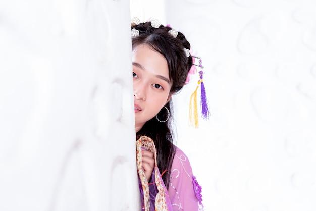 Азиатская девушка в традиционных китайских платьях заглядывает за белую стену Premium Фотографии