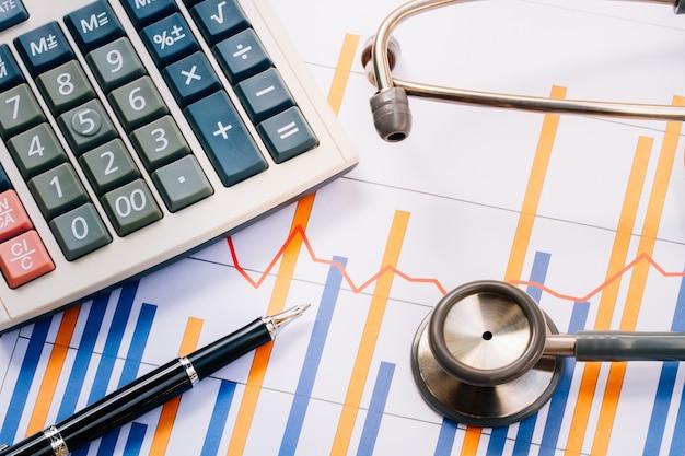 医療用ヘッドホン、机の上に財務報告書の図表と電卓を備えた聴診器 Premium写真