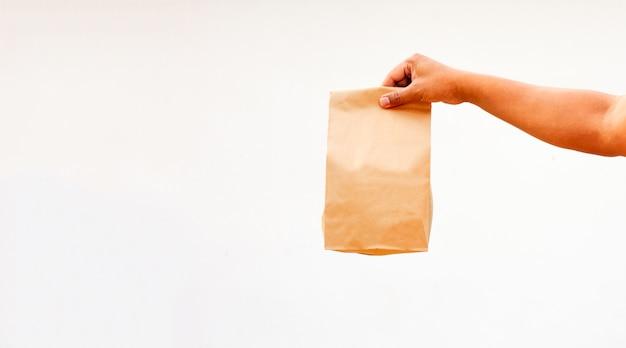 人は持ち帰り用の茶色の空のクラフト紙袋を保持 Premium写真