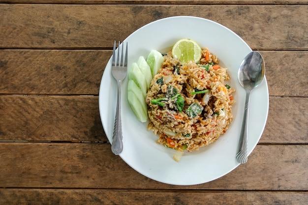 Жареный рис, куриное яйцо и овощная морковь, китайская капуста, зеленый лук и огурец на тарелке Premium Фотографии