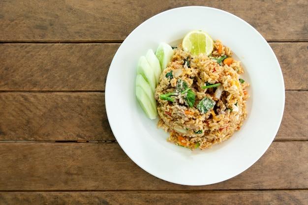 Жареный рис, куриное яйцо и овощная морковь, китайская капуста, зеленый лук и огурец на тарелке - тайская еда Premium Фотографии