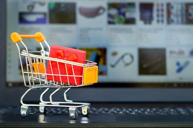 オンラインショッピングの概念。ショッピングカート、小さな箱、机の上のノートパソコン Premium写真