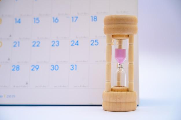カレンダーのアイデアと砂時計、各期間と予定の経過日数または待機 Premium写真