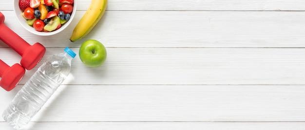 健康的な果物。新鮮なフルーツサラダダイエットスリムフィットダンベルスポーツ用品木製テーブルの背景に Premium写真