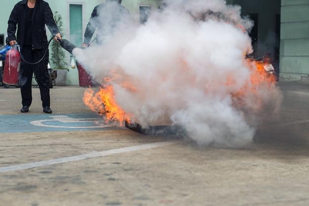 消火器を持っていると燃える火にスプレーの手 Premium写真