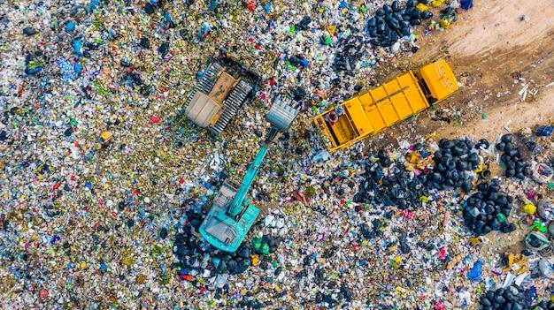 ゴミ捨て場やゴミ捨て場にゴミ杭、空撮ゴミ収集車はゴミを埋め立て地に降ろします。 Premium写真
