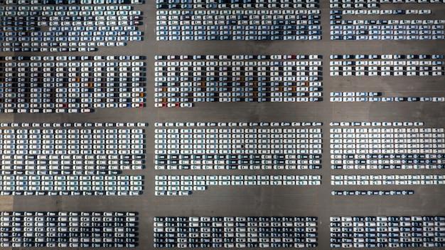 ビジネスカーの輸出入物流のために港に並ぶ新車、空撮。 Premium写真