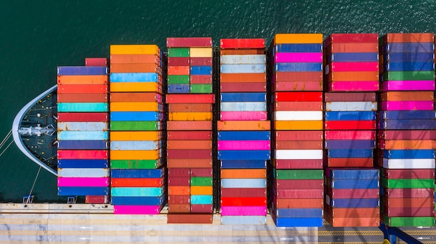 深海港でのコンテナ船の積み下ろし、ビジネスロジスティックのインポートとエクスポートの空中上面図 Premium写真