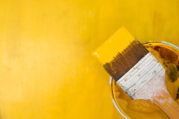 ブラシから飛び散る黄色の塗料。 Premium写真