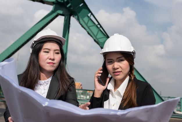女性エンジニアは、ラジオ、青写真、レポート、電力業界の従業員の管理スケジュールを保持しています。 Premium写真
