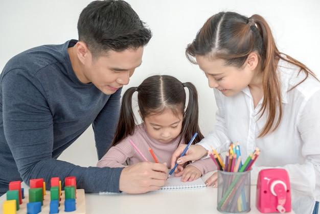 母と父は娘が居間で宿題をするのを手伝います Premium写真