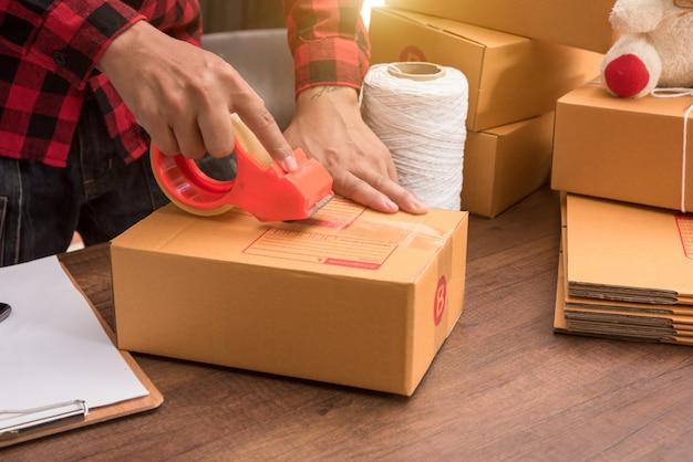 Молодая рука женщина готовит пакет для отправки на деревянный пол Premium Фотографии