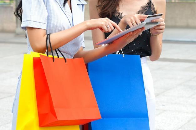 買い物袋とタブレットを使用している女性 Premium写真