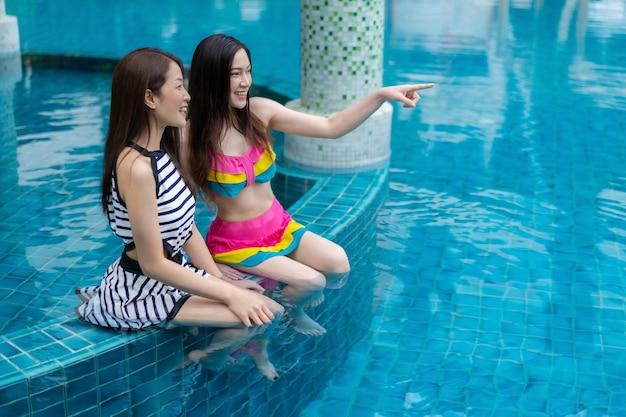 Две молодые женщины-друзья пользуются в бассейне Premium Фотографии