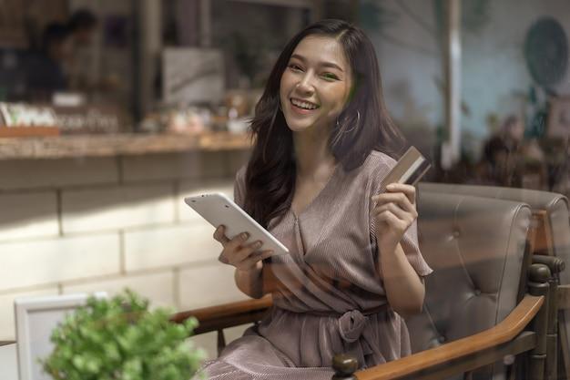 カフェでタブレットでオンラインショッピングにクレジットカードを使用している幸せな女性 Premium写真