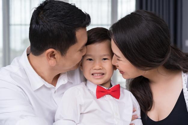 幸せな家族の概念、妊娠中の母親と父親の子供男の子にキス Premium写真