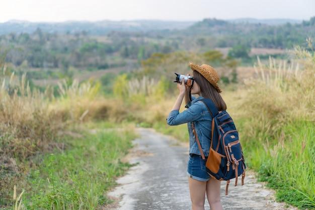 Туристская женщина принимая фото с ее камерой в природе Premium Фотографии