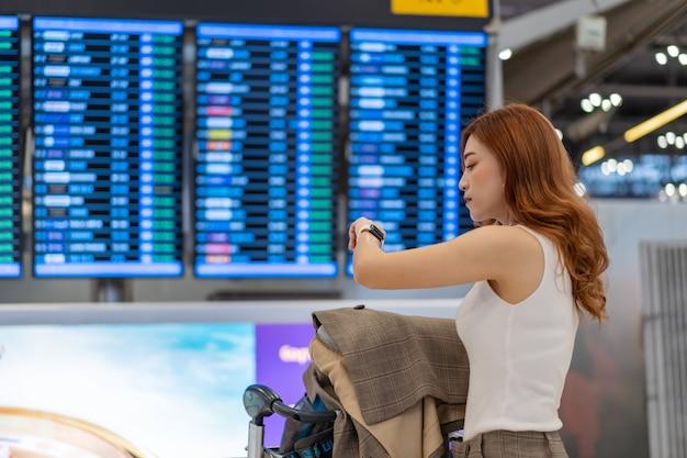 Женщина смотрит на свои умные часы с табло информации о рейсах в аэропорту Premium Фотографии