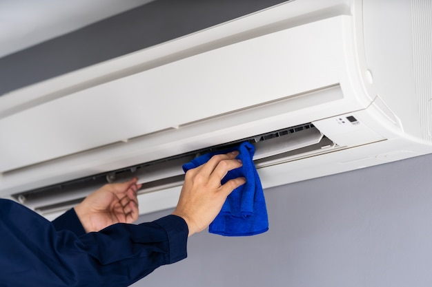 布でエアコンを掃除する技術者サービスを閉じる Premium写真