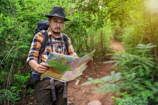 バックパックとマップ検索方向の森の男性旅行者 Premium写真