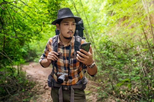 Человек путешественник с рюкзаком, используя смартфон в лесу Premium Фотографии