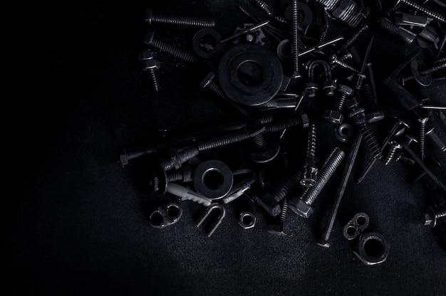 暗い背景に使用される金属ねじナットと釘ボルトの概要 Premium写真