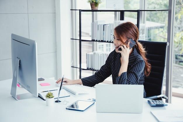 Коммерсантка используя мобильный телефон пока работающ в ее офисе. Premium Фотографии