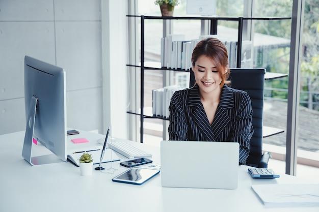 彼女のオフィスで働いている間ラップトップを使用して実業家。 Premium写真