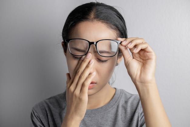 Женщины держат очки и страдают от болей в глазах. Premium Фотографии