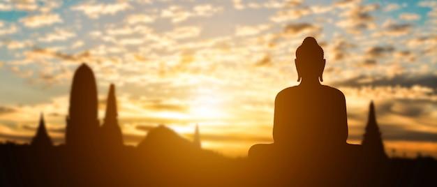 Силуэт будды на закате золотой храм. туристический аттракцион в таиланде. Premium Фотографии