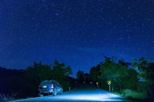 Много звезд на ночном небе с автомобилем на дороге Premium Фотографии